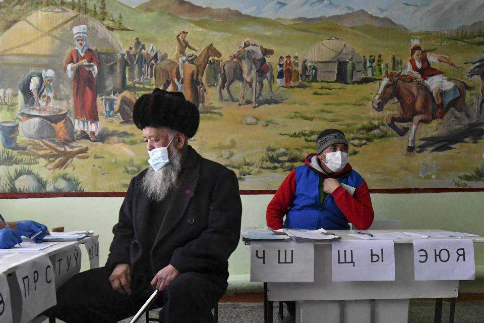 An elderly man wearing a face mask to protect against coronavirus, left, waits to get his ballot at a polling station during the presidential elections in Gornaya Maevka village, about 25 kilometers (16 miles) south-west of Bishkek, Kyrgyzstan, Sunday, Jan. 10, 2021. Voters in Kyrgyzstan are casting ballots in an early presidential election that follows the ouster of the nation's previous president. President Sooronbai Jeenbekov was forced to step down on Oct. 15 under pressure from demonstrators who challenged the results of a parliamentary vote earlier that month. (AP Photo/Vladimir Voronin)