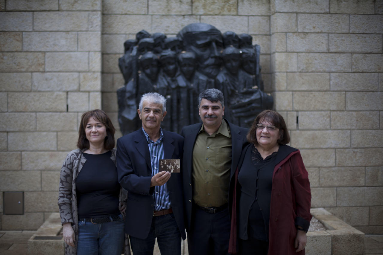 Israeli Dorit Korenblum, left, her brother Refael Korenblum, and sister, Bracha Fleishman-Korenblum, right pose for picture after uniting with their cousin Gennadiy Koramblyum of Queens, New York, while holding a picture of the Korenblum family at the Yad Vashem Holocaust memorial in Jerusalem, Thursday, Nov. 17, 2011. For five long years during World War II, Nahum Korenblum never left the side of his younger brother Yaakov as the two fled the Nazis in Poland, escaped forced labor camps across Europe and ultimately joined the Soviet Red Army. There, they were separated and dispatched abroad, never to meet again. On Thursday, more than a decade after they died, their children were united at Israel's Yad Vashem Holocaust memorial thanks to a recently uploaded family photo discovered on the its comprehensive online database of Holocaust victims.(AP Photo/Bernat Armangue)