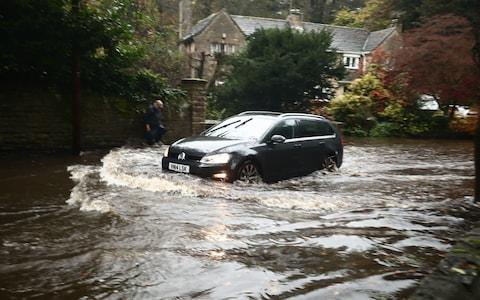 A car passing through a flooded road in Whirlow, Sheffield - Credit: PA