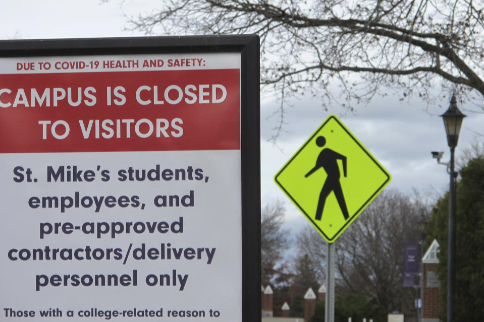 FILE - In this Nov. 12, 2020, file photo, a sign at the entranceway to St. Michael's College in Colchester, Vt., says that the campus is closed to visitors due to a COVID-19 outbreak. Colleges throughout the U.S. are assuring students that this coming fall will bring a return to in-person classes, intramural sports and mostly full dormitories. But those promises come with asterisks. (AP Photo/Lisa Rathke)