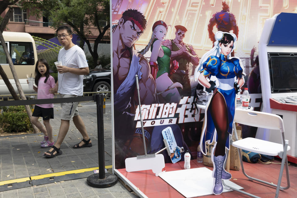 A man and a child past by a promotion for computer games in Beijing on Saturday, Aug. 29, 2020. China is banning children from playing online games for more than three hours a week, the harshest restriction so far on the game industry as Chinese regulators continue cracking down on the technology sector. (AP Photo/Ng Han Guan)