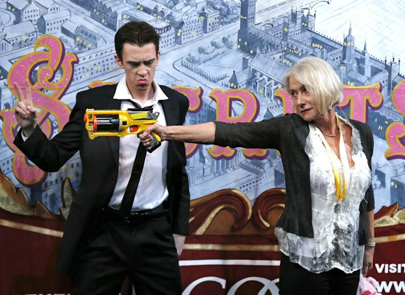 Actress Helen Mirren fires a toy gun next to actor Sam Clark who plays an Al Pacino character during her roast as woman of the year by Harvard University's Hasty Pudding Theatricals in Cambridge, Mass., Thursday, Jan. 30, 2014. (AP Photo)