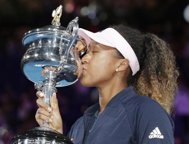 Japan's Naomi Osaka kisses her trophy after defeating Petra Kvitova of the Czech Republic during the women's singles final at the Australian Open tennis championships in Melbourne, Australia, Saturday, Jan. 26, 2019.(AP Photo/Aaron Favila)