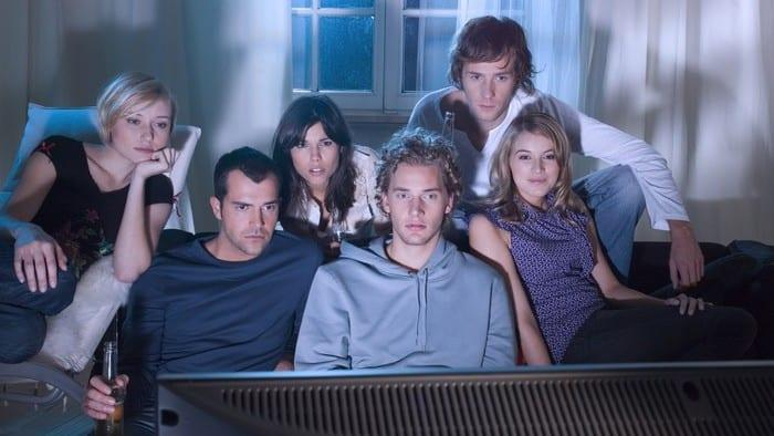 Group of young adults around a TV watching Netflix