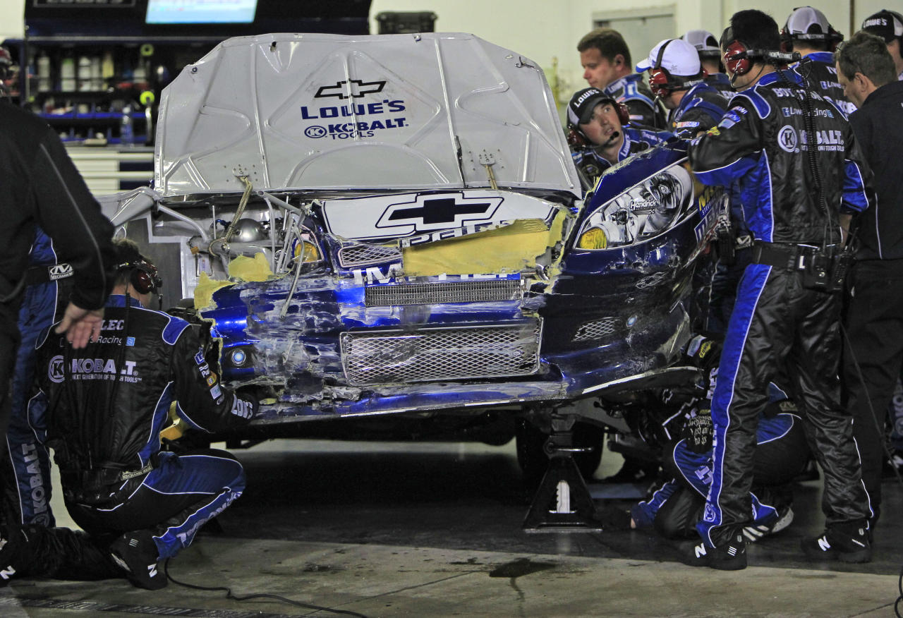 Crew members work on the car of driver Jimmie Johnson after a crash during the NASCAR Daytona 500 auto race at Daytona International Speedway in Daytona Beach, Fla., Monday, Feb. 27, 2012. (AP Photo/John Raoux)