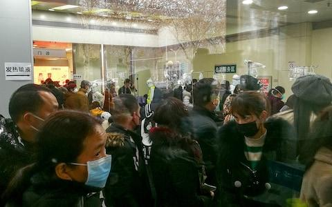 People queue for receiving treatment at the fever outpatient department at the Wuhan Tongji Hospital - Credit: Reuters