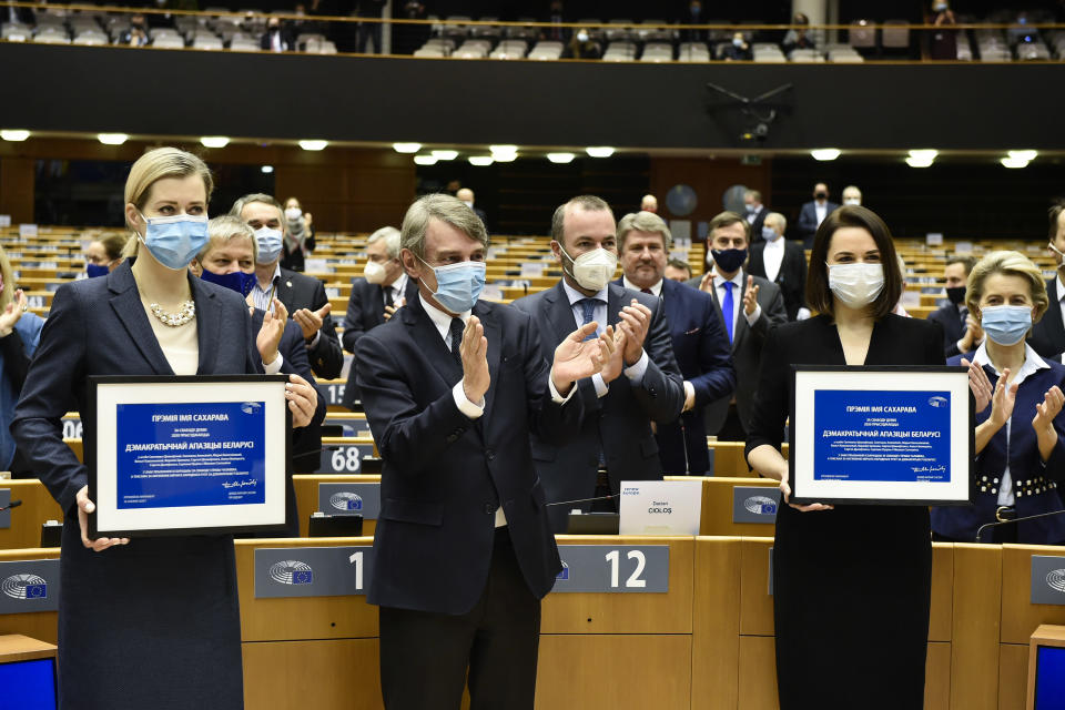 European Parliament President David Sassoli, center, applauds as Belarus opposition leaders Veranika Tsapkala, left, and Svetlana Tikhanovskaya, right, hold their prizes during the Sakharov Prize ceremony at the European Parliament in Brussels, Wednesday, Dec 16, 2020. The European Union has awarded its top human rights prize to the Belarusian democratic opposition. (John Thys/Pool Photo via AP)
