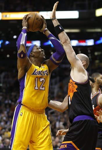 Los Angeles Lakers' Dwight Howard (12) shoots over Phoenix Suns' Marcin Gortat during the first half of an NBA basketball game, Wednesday, Jan. 30, 2013, in Phoenix. (AP Photo/Matt York)
