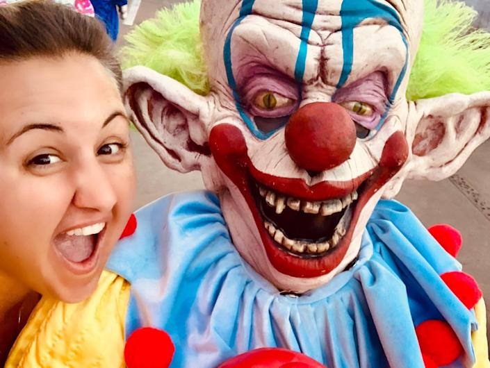 Carly Caramanna next to a scary clown at universal's halloween horror nights
