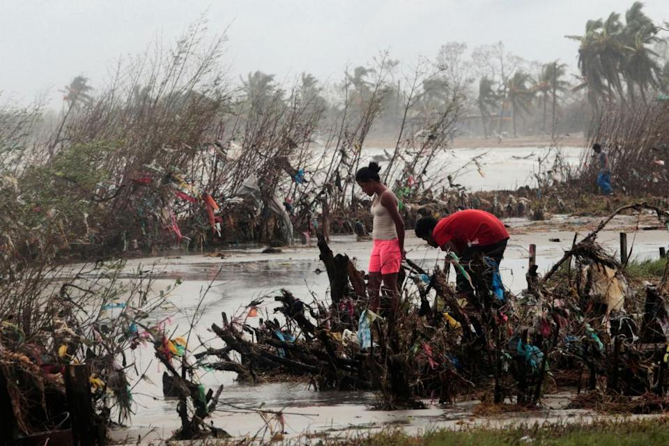 Residents inspect an area filled with plastic rubbish after the passing of Hurricane Iota, in Puerto Cabezas, Nicaragua.