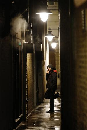 A man smokes in an alley behind his place of work in London