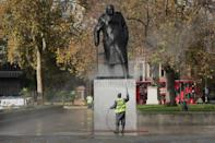 A workman uses a water jet spray to clean the statue of Sir Winston Churchill in Parliament Square
