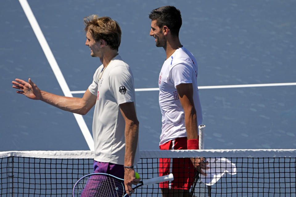 Novak Djokovic, of Serbia, right, and Alexander Zverev, of Germany, walk off the court after their practice for the men's tennis competition at the 2020 Summer Olympics, Thursday, July 22, 2021, in Tokyo. (AP Photo/Charlie Riedel)