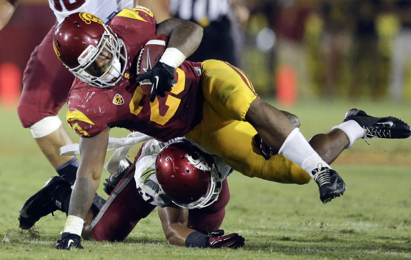 Southern California running back Tre Madden, top, is tackled by Washington State linebacker Cyrus Coen during the second half of an NCAA college football game in Los Angeles, Saturday, Sept. 7, 2013. (AP Photo/Chris Carlson)