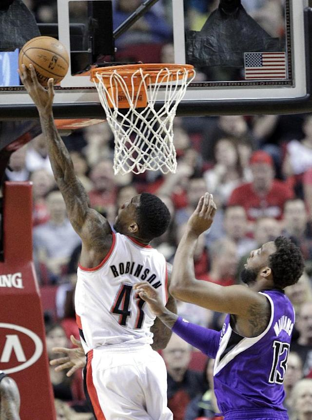 Portland Trail Blazers forward Thomas Robinson, left, goes to the hoop past Sacramento Kings forward Derrick Williams during the first half of an NBA basketball game in Portland, Ore., Wednesday, April 9, 2014. (AP Photo/Don Ryan)