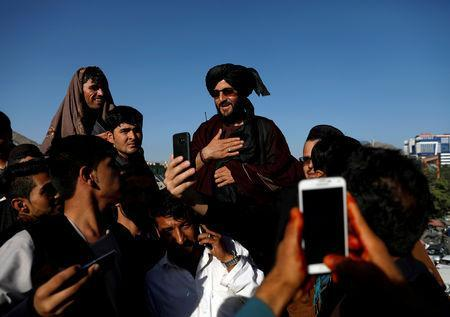 FILE PHOTO: People take selfies with a Taliban in Kabul, Afghanistan June 16, 2018. REUTERS/Mohammad Ismail/File Photo