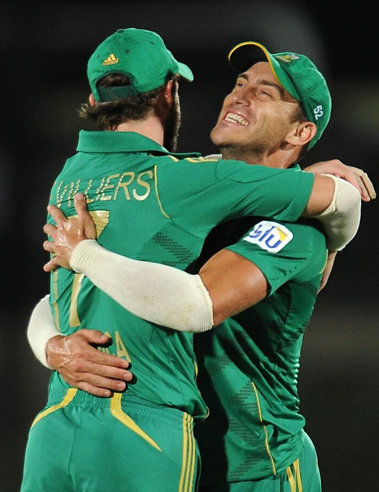 South African cricket captain Faf du Plessis (R) celebrates with his teammate AB de Villiers (L) after victory in the second Twenty20 cricket match between Sri Lanka and South Africa at the Suriyawewa Mahinda Rajapakse International Cricket Stadium in the southern district of Hambantota on August 4,2013. AFP PHOTO / LAKRUWAN WANNIARACHCHi