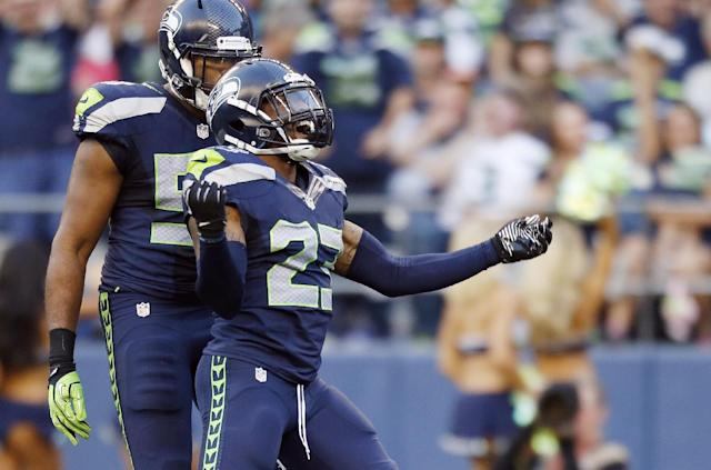 Seattle Seahawks strong safety Jeron Johnson (23) celebrates a tackle with outside linebacker K.J. Wright, left, in the first half of a preseason NFL football game against the San Diego Chargers, Friday, Aug. 15, 2014, in Seattle. (AP Photo/John Froschauer)