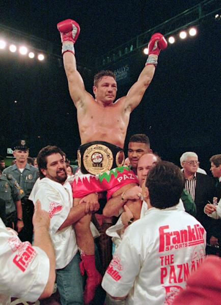 """FILE - In this Aug. 23, 1996 file photo, boxer Vinny Pazienza, of Providence, R.I., is lifted up after winning a 12 round WBU super middleweight title bout against Dana Rosenblatt in Atlantic City, N.J. A new film, """"Bleed For This,"""" based on Pazienza's life, opens November 18. (AP Photo/Bill Borrelli, File)"""