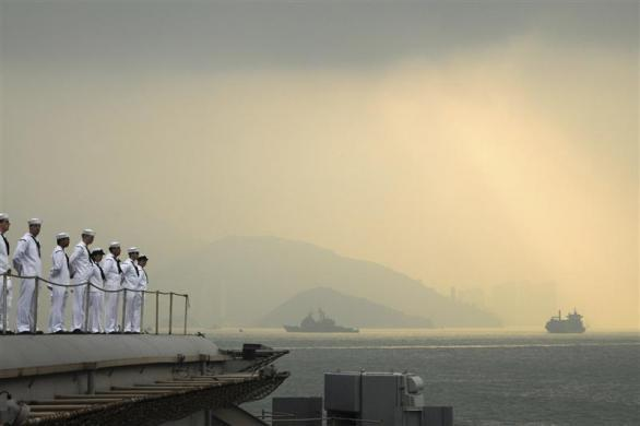 Sailors aboard the aircraft carrier USS George Washington man the rails as the ship pulls out of Hong Kong after a five-day port visit in this U.S. Navy handout photo dated November 14, 2011.
