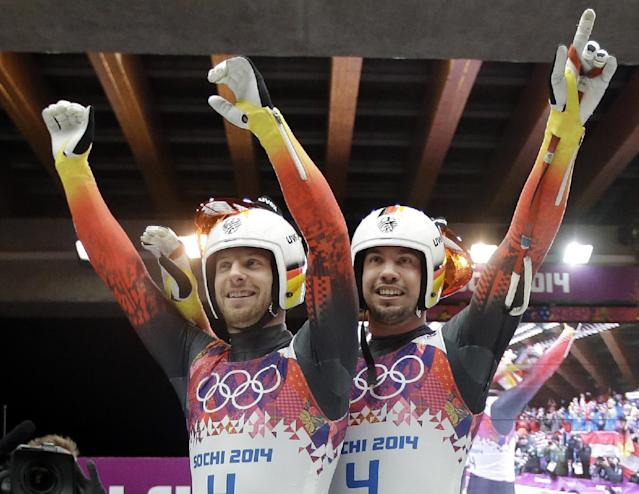 The doubles team of Tobias Wendl and Tobias Arlt from Germany celebrate in the finish area after their final run to win the gold medal during the men's doubles luge at the 2014 Winter Olympics, Wednesday, Feb. 12, 2014, in Krasnaya Polyana, Russia. (AP Photo/Dita Alangkara)