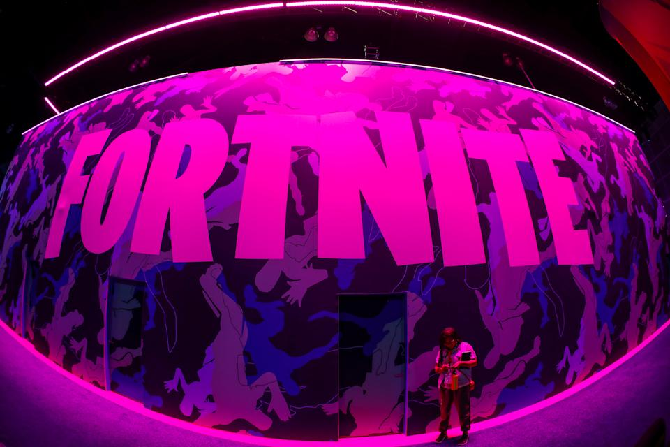 An attendee stops to text next to Epic Games Fortnite sign at E3, the annual video games expo revealing the latest in gaming software and hardware in Los Angeles, California, U.S., June 12, 2019.  REUTERS/Mike Blake