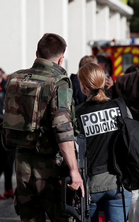 A police investigator and an armed soldier work near the scene where French soliders were hit and injured - Credit: REUTERS/Benoit Tessier