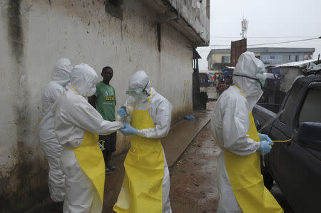 Health workers wearing protective clothing prepare before carrying an abandoned dead body presenting with Ebola symptoms at Duwala market in Monrovia