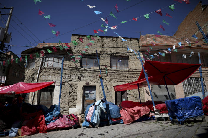 A woman, without anything to sell, cover her market stall in La Paz, Bolivia, Monday, Nov. 18, 2019. The blockades of former president Evo Morales' supporters on the outskirts of the main cities of Bolivia are causing a shortage of gasoline and food. People say markets are short of fruits and vegetables. (AP Photo/Natacha Pisarenko)