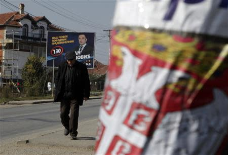 A Kosovar Serb walks past election campaign posters of Samostalna Liberalna Stranka (Independent Liberal Party) and Gradanska inicijativa Srbija (R) (Serbian Citizens' Initiative) in the town of Gracanica, which is largely inhabited by Serbians, November 2, 2013. REUTERS/Hazir Reka