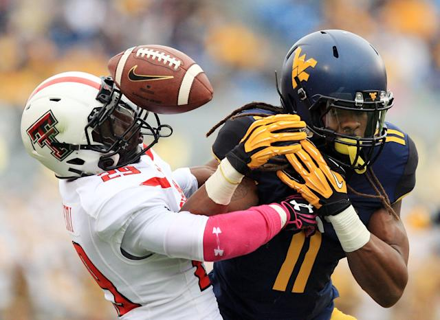 Texas Tech's Olauluwa Falemi (29) breaks up a pass intended for West Virginia's Kevin White (11) during the second quarter of an NCAA college football game in Morgantown, W.Va., on Saturday, Oct. 19, 2013. (AP Photo/Christopher Jackson)