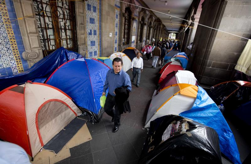 A man walks between tents installed by protesting teachers at the Zocalo plaza in Mexico City, Friday, Aug. 30, 2013. Teachers' protests that have snarled traffic, blocked government buildings and caused the cancellation of sports events in Mexico City have prompted President Enrique Pena Nieto to change the date of his state-of-the-union address. (AP Photo/Eduardo Verdugo)
