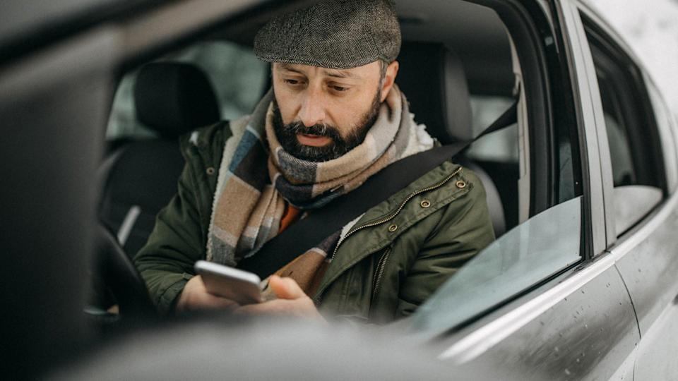 Man driving car and using phone to send text message.
