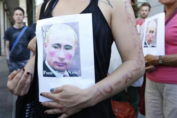 Activists hold banners depicting Russian President Vladimir Putin during a protest in support of members of the female punk band Pussy Riot in front of the Russian delegation to the European Union in Brussels August 17, 2012.
