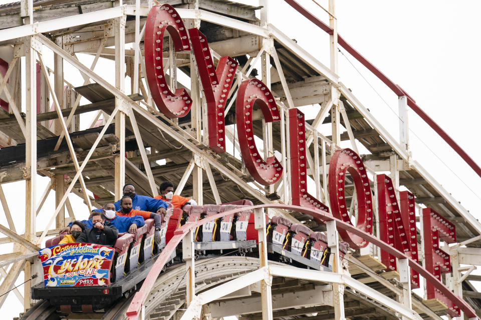 The Cyclone rollercoaster begins taking passengers after the seasonal opening of the Coney Island amusement park area, Friday, April 9, 2021, in the Brooklyn borough of New York. Coney Island's illustrious amusement parks are reopening Friday after the coronavirus pandemic shuttered them all last year. (AP Photo/John Minchillo)