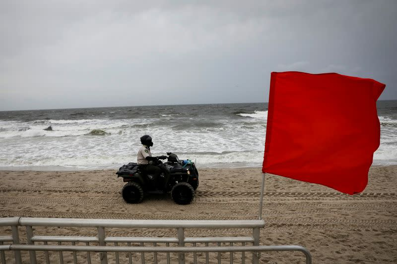 A New York City Park Ranger patrols the beach ahead of Tropical Storm Isaias in the Rockaway area of Queens in New York