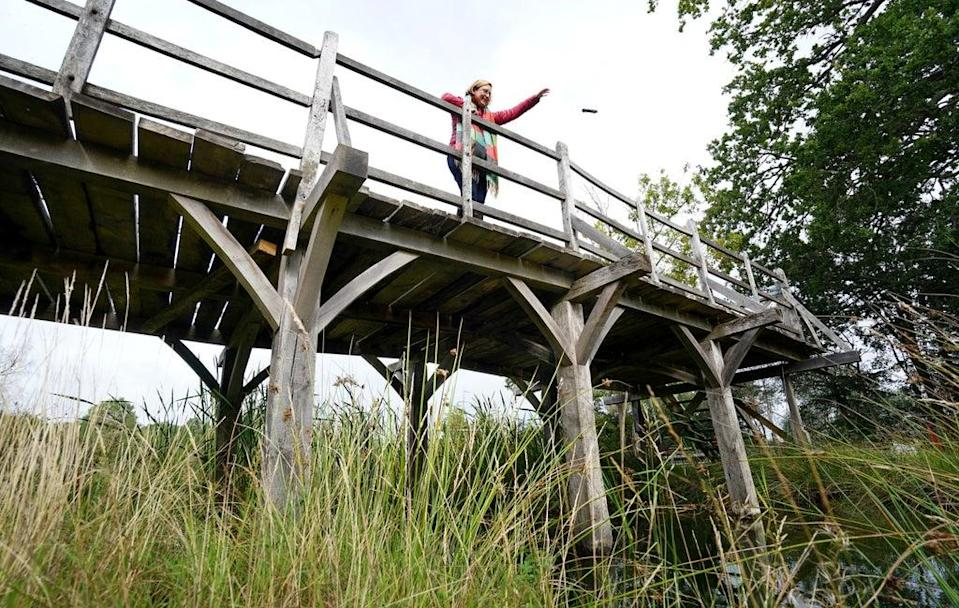 Silke Lohmann of Summers Place Auctions stands on the original Poohsticks Bridge from Ashdown Forest (Gareth Fuller/PA) (PA Wire)