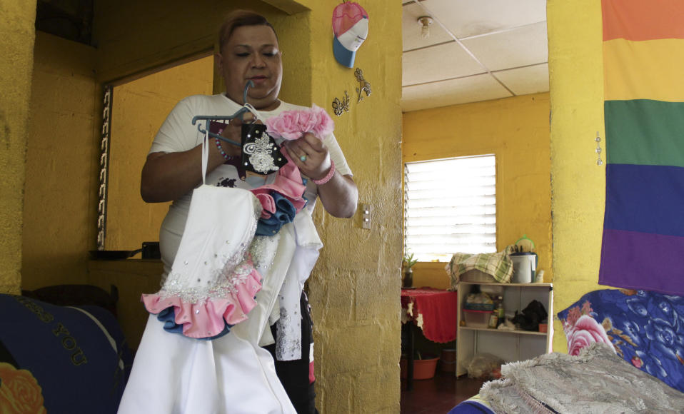 """Venus Nolasco, director of the San Miguel LGBTQ collective """"Pearls of the East,"""" holds the parade costume that his friend Zashy Zuley del Cid Velasquez would wear on International Day Against Homophobia, in San Miguel, El Salvador, Tuesday, May 25, 2021. Del Cid was shot in the back walking alone at night down the street. Passersby tried to help her and took her to a local hospital where she died on April 25. So far, police have made no arrests and Nolasco believes that like other hate crimes in the country """"it will be forgotten; they're not interested in what happens to us."""" (AP Photo/Salvador Melendez)"""