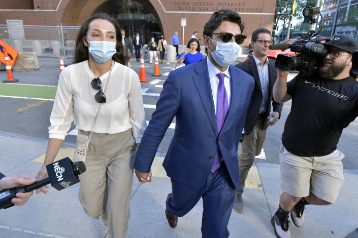 Former Fall River, Mass. Mayor Jasiel Correia and his wife Jenny Fernandes, left, leave a court appearance at the John Joseph Moakley United States Courthouse, Monday, Sept. 20, 2021, in Boston. A federal judge said he planned to toss several convictions against the Massachusetts mayor elected at just 23 years old who was found guilty by jurors of bilking investors and extorting hundreds of thousands of dollars from marijuana businesses. (AP Photo/Josh Reynolds)