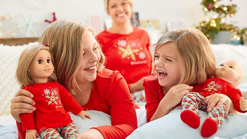 Two girls in matching outfits laughing and playing with American Girl dolls while their mother watches from a distance