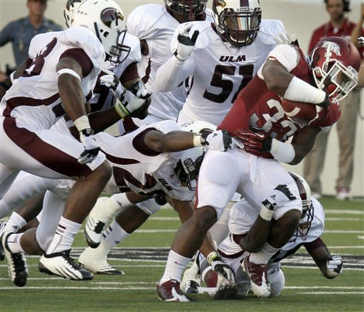 Arkansas running back Dennis Johnson (33) pushes past Louisiana Monroe linebacker R.J. Young (51), Louisiana Monroe's Conner Fryoux, bottom right, safety Isaiah Newsome, center, and safety Mitch Lane, left, during the second quarter of an NCAA college football game in Little Rock, Ark., Saturday, Sept. 8, 2012. (AP Photo/Danny Johnston)