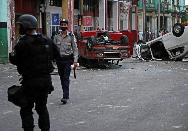 Police cars are seen overturned in the street in the framework of a demonstration against Cuban President Miguel Diaz-Canel in Havana, on July 11, 2021. - Thousands of Cubans took part in rare protests Sunday against the communist government, marching through a town chanting