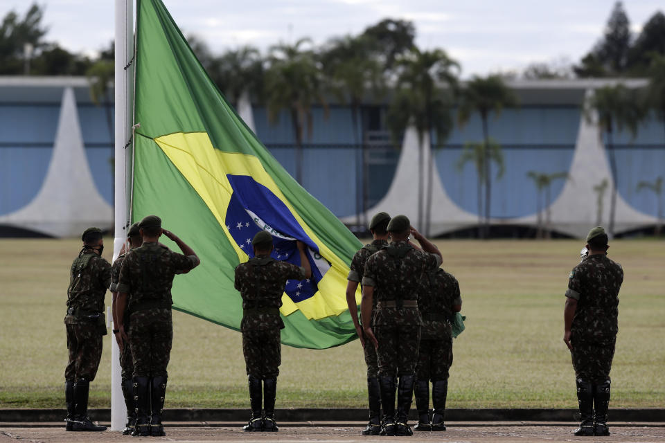 Soldiers hold the flag-raising ceremony outside the president's official residence, Alvorada Palace, in Brasilia, Brazil, Wednesday, July 8, 2020. Brazil's President Jair Bolsonaro said Tuesday he tested positive for COVID-19. (AP Photo/Eraldo Peres)
