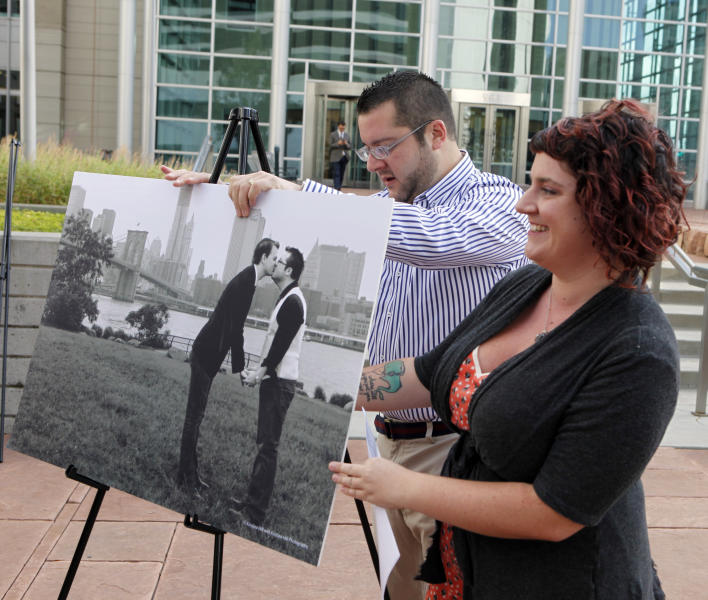 Tom Privitere helps photographer Kristina Hill setup a photograph of himself and his partner Brian Edwards outside the federal courthouse in Denver on Wednesday, Sept. 26, 2012. Privitere, Edwards and Hill filed a lawsuit in federal court on Wednesday over the fact that the photo was altered and used in a political campaign in Colorado. (AP Photo/Ed Andrieski)