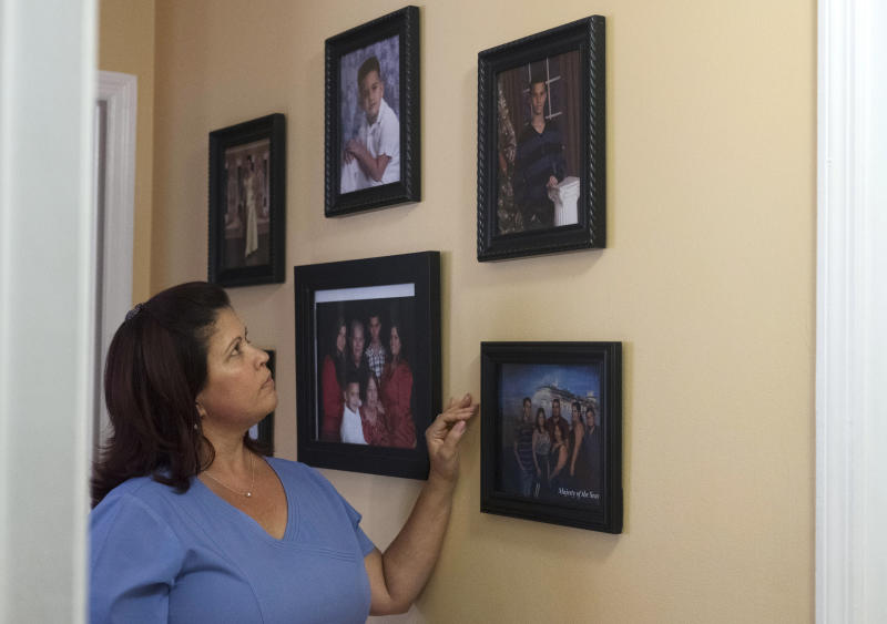 In this July 3, 2019, photo, Milankys Lazo looks at an old photo of her son, Andy Vila, hanging the wall of on home in Miami. Lazo, who immigrated from Cuba to the United States, says she disagrees with her socialist son's politics. She said his beliefs have caused great tension and many arguments between the two. (AP Photo/Ellis Rua)