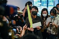 Pro-democracy lawmaker Claudia Mo holds a yellow umbrella and her resignation letter at the Legislative Council in Hong Kong -- she is one of more than a dozen expected to resign