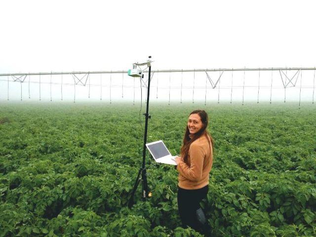 A Prospera scientist working with a camera mounted on a movable sprinkler system.