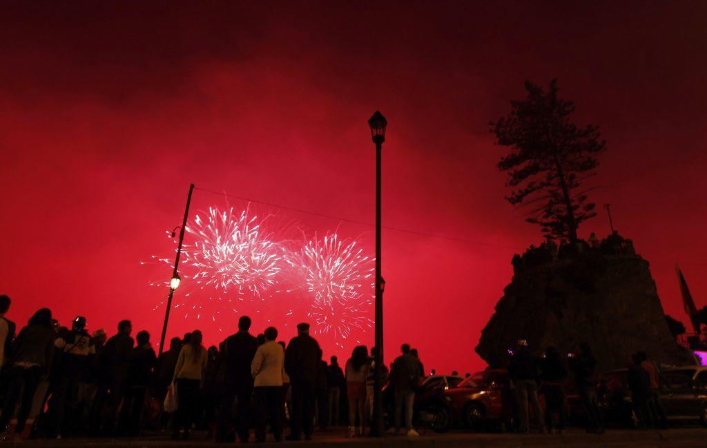People watch as fireworks explode over the coast of Vina del Mar, Chile as part of the New Year celebrations, January 1, 2013.