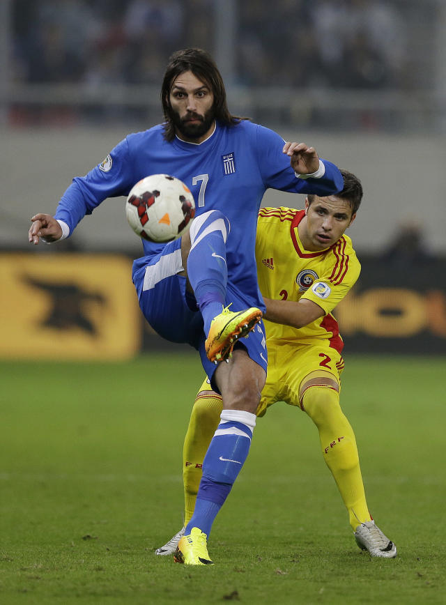 FILE - In this v, file photo, Greece's Giorgos Samaras, left, controls the ball as Romania's Alexandru Matel Torje tries to stop him during their World Cup qualifying playoff first leg soccer match at the Karaiskaki stadium in the port of Piraeus, near Athens. Greece coach Fernando Santos will step down after the World Cup, but says he's glad to help lift the country's spirits after it endured four years of severe financial crisis. (AP Photo/Thanassis Stavrakis, File)