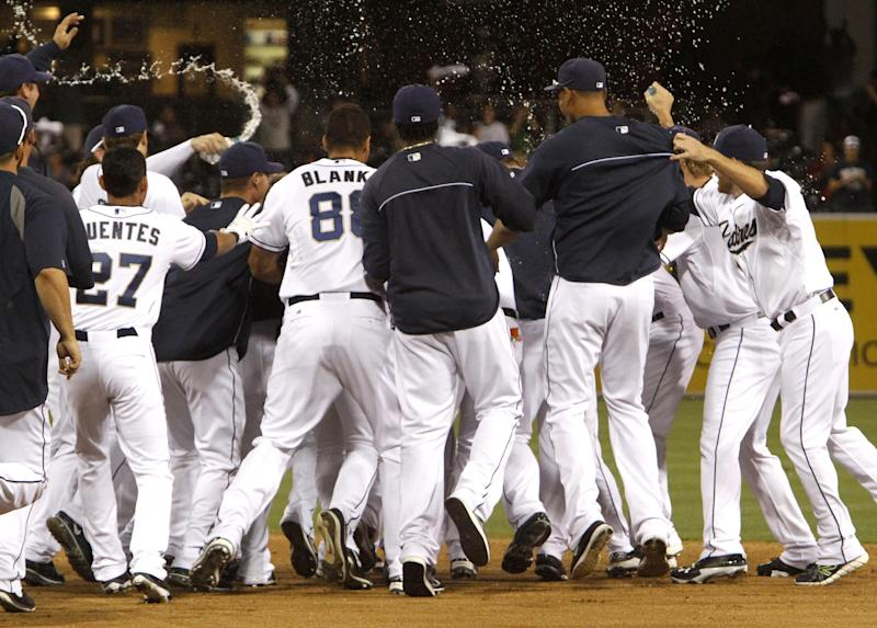 San Diego Padres teammates celebrate with Alexi Amarista after his walk-off hit with bases loaded in the eleventh inning during a baseball game against Arizona Diamondbacks on Thursday, Sept. 26, 2013, in San Diego. The San Diego Padres won 3-2. (AP Photo/Don Boomer)